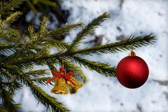 Composición de la Navidad con el árbol de abeto, la bola roja y las campanas Fondo blanco de la nieve Fotografía de archivo libre de regalías