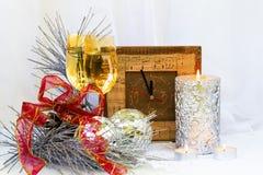 Composición de la Navidad con el reloj, vidrios y una vela de plata gruesa… Fotos de archivo