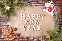 Composición de la Navidad con el texto en la Feliz Año Nuevo de papel en el centro del bastidor Imagenes de archivo