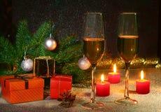 Composición de la Navidad con el vidrio del vino o del coñac chispeante, velas de la Navidad, bolas coloridas, caja del champán d Imagen de archivo