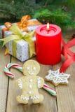 Composición de la Navidad con la caja de regalo, el hombre de pan de jengibre, los bastones de caramelo y la vela Foto de archivo libre de regalías