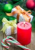 Composición de la Navidad con la caja de regalo, los bastones de caramelo y la vela Imagenes de archivo