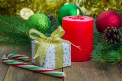 Composición de la Navidad con la caja de regalo, los bastones de caramelo y la vela Imágenes de archivo libres de regalías