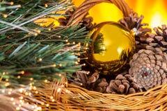 Composición de la Navidad con la cesta con los conos y el oro Chris del pino Fotografía de archivo
