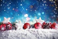 Composición de la Navidad con las bolas, las estrellas y las guirnaldas en nieve Foto de archivo