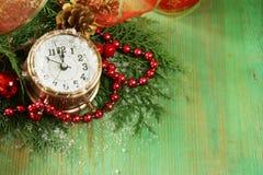 Composición de la Navidad con las ramas, las decoraciones y el reloj del abeto Imágenes de archivo libres de regalías