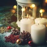 Composición de la Navidad con las velas y las decoraciones ardientes Foto de archivo libre de regalías