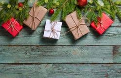 Composición de la Navidad con los presentes y las ramas del abeto en el tablero de madera de la turquesa rústica fotografía de archivo libre de regalías