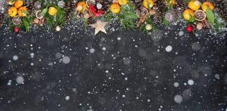 Composición de la Navidad con la rama del árbol de navidad, mandarinas, ornamentos de la Navidad, conos del pino en un fondo negr Imagenes de archivo