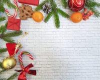 Composición de la Navidad el regalo, conos del pino, pan de jengibre, abeto ramifica con el fondo del blanco del ladrillo de la p Imagenes de archivo