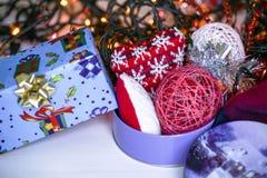 Composición de la Navidad en bolas rojas del fondo de madera, los regalos, y la rama de árbol de navidad verde con los conos, vel Foto de archivo libre de regalías