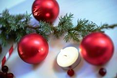 Composición de la Navidad en fondo de madera con las bolas y el árbol de navidad verde con los conos del pino, vela ardiente de l Imágenes de archivo libres de regalías