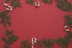 Composición de la Navidad hecha de las ramitas del thuja y de los bastones de caramelo verdes en fondo rojo Visión superior, ende Imagen de archivo