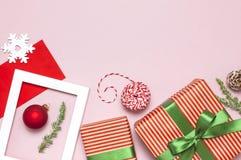 Composición de la Navidad Marco blanco de la foto, sobre rojo, ramas del abeto, conos, bola, guita, regalo, juguetes de madera en imagenes de archivo