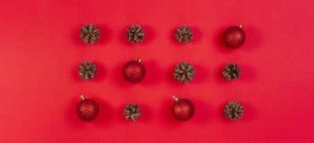 Composición de la Navidad Modelo hecho de conos del pino y de la decoración roja de la Navidad en fondo rojo Visión superior, end fotos de archivo