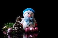 Composición de la Navidad: muñeco de nieve, bolas de la Navidad, e isolat del cono Foto de archivo