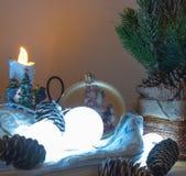 Composición de la Navidad o del Año Nuevo con el gerland ardiendo, los conos y las bayas rojas, fondo oscuro del bosque, foco sel imágenes de archivo libres de regalías