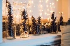 Composición de la Navidad o del Año Nuevo con las guirnaldas en pequeños palmatorias y conos de cristal del pino, barras de mader Imagenes de archivo