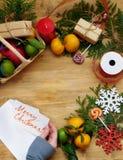 Composición de la Navidad que consiste en la fruta cítrica, los dulces, las ramas del thuja y las actuales cajas Imagenes de archivo