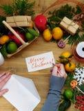 Composición de la Navidad que consiste en la fruta cítrica, los dulces, las ramas del thuja y las actuales cajas Imágenes de archivo libres de regalías