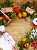 Composición de la Navidad que consiste en la fruta cítrica, los dulces, las ramas del thuja y las actuales cajas Imagen de archivo libre de regalías