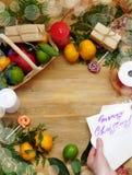 Composición de la Navidad que consiste en la fruta cítrica, los dulces, las ramas del thuja y las actuales cajas Concepto de emba Foto de archivo libre de regalías