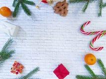 Composición de la Navidad Regalo de Navidad, conos del pino, ramas spruce en un fondo del blanco del ladrillo Visión plana, super Imagenes de archivo