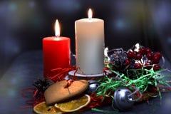 Composición de la Navidad: velas ardientes rojas y blancas en una tabla festiva en un fondo oscuro Pan de jengibre, malla, adorno fotos de archivo libres de regalías