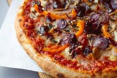 Composición de la pizza en la tabla de madera con el fondo gris imagen de archivo