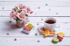 Composición de la primavera: una taza de té, galletas de almendra, flores brillantes Foto de archivo libre de regalías