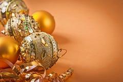 Composición de las bolas de oro de la Navidad en fondo marrón claro Imagen de archivo libre de regalías