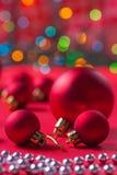 Composición de las bolas rojas de la Navidad en la tabla roja Imagen de archivo