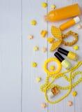 Composición de los accesorios amarillos para la chica joven o el adolescente Esmaltes de uñas, lápiz labial, pinzas de pelo, band Foto de archivo libre de regalías