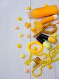 Composición de los accesorios amarillos para la chica joven o el adolescente Esmaltes de uñas, lápiz labial, pinzas de pelo, band Imágenes de archivo libres de regalías