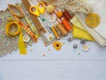 Composición de los accesorios amarillos para la costura en fondo de madera El hacer punto, bordado, cosiendo Pequeña empresa Rent Fotografía de archivo libre de regalías