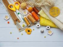 Composición de los accesorios amarillos para la costura en fondo de madera El hacer punto, bordado, cosiendo Pequeña empresa Rent Foto de archivo libre de regalías