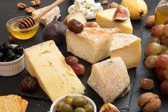 Composición de los alimentos con los bloques de queso mohoso, ciruelos conservados en vinagre, hon Imagen de archivo