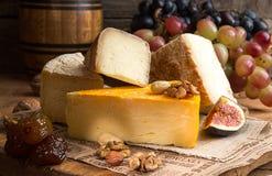 Composición de los alimentos con los bloques de queso mohoso, fechas secadas, uva Fotos de archivo libres de regalías