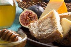 Composición de los alimentos con el pedazo de queso mohoso, miel, higos Imágenes de archivo libres de regalías