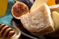 Composición de los alimentos con el pedazo de queso mohoso, miel, higos Imagen de archivo libre de regalías