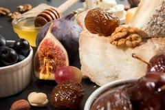 Composición de los alimentos con el pedazo de queso, uva, fechas, aceitunas, wa Imágenes de archivo libres de regalías