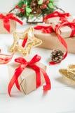 Composición de los días de fiesta de la Navidad con los regalos en papel del arte con la cinta de satén roja en el fondo de mader Imagenes de archivo
