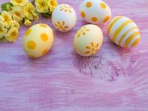 Composición de los huevos de Pascua y de las flores de la primavera en el woode violeta Imagenes de archivo