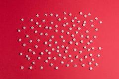 Composición de los pequeños copos de nieve en la tabla roja fotos de archivo