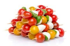 Composición de los tomates de cereza y de la mozzarella en los pinchos Foto de archivo libre de regalías