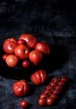 Composición de los tomates en fondo negro Imagen de archivo