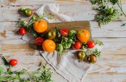 Composición de los tomates maduros coloridos del verano flatlay Fondo de madera del vintage blanco Fotos de archivo libres de regalías