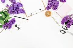 Composición de Minimalistic con el tablero, el cuaderno, las flores de la lila, la caja de regalo y los accesorios en fondo de ma Fotografía de archivo