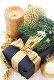 Composición de oro de la Navidad con la caja, la vela y la rama de regalo de Fotos de archivo libres de regalías