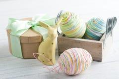 Composición de Pascua con el regalo, el conejo del juguete y los huevos Fotografía de archivo libre de regalías
